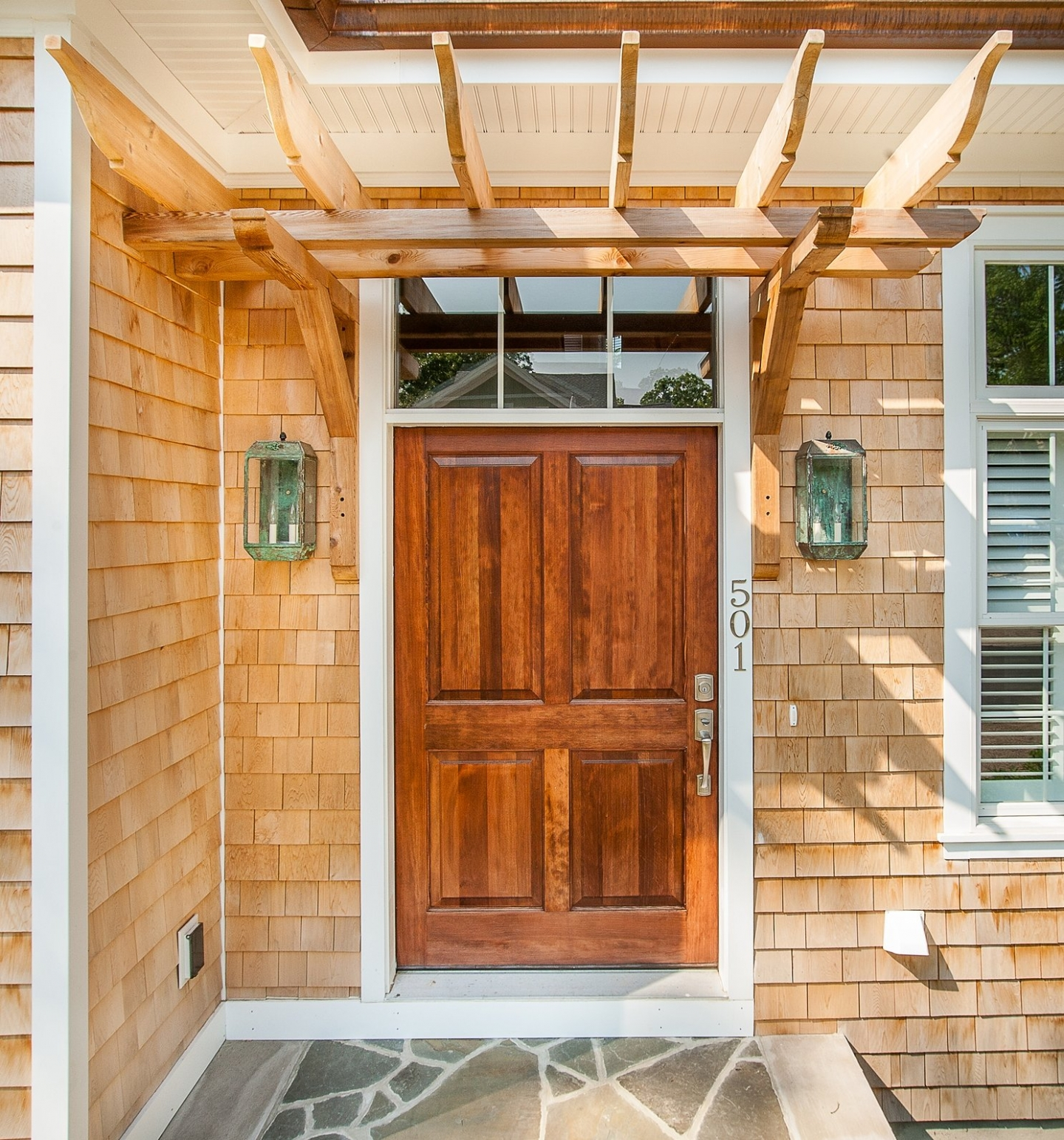 Red wood exterior doors available with custom stain colors and antique light fixtures and cedar arbor